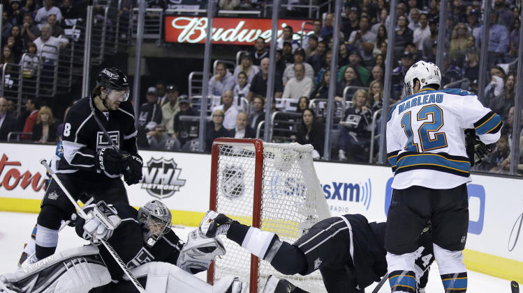 Los Angeles Kings goalie Jonathan Quick stops a shot on goal by San Jose Sharks' Patrick Marleau (12) as Kings' Drew Doughty, left, and Robyn Regehr defend during the first period in Game 1 of a second-round NHL hockey Stanley Cup playoff series in Los Angeles, Tuesday, May 14, 2013. (AP Photo/Chris Carlson)