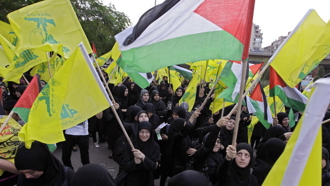 In this photo taken on Saturday, Nov. 17, 2012, Hezbollah supporters wave Hezbollah and Palestinian flags during a demonstration against the Israeli offensive in Gaza organized by Palestinian groups and the Lebanese militant Hezbollah group, near the U.N. headquarters in Beirut, Lebanon. With the death toll from the Israel-Gaza conflict mounting, Hezbollah has offered quiet words of encouragement to the Palestinians, pledging support and calling on Arab states to send them weapons to fight Israel. But beyond that, the Lebanese militant group appears to be staying firmly on the sidelines. (AP Photo/Bilal Hussein)