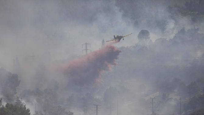 A fire plane drops fire retardant to extinguish fire burning in the forest in Jerusalem, Tuesday, June. 26, 2012. Two large forest fires on the outskirts of Jerusalem snarled traffic wafting smoke across the city and temporarily closed the main highway with Tel Aviv. Last week, the governments watchdog agency issued a report that blamed senior government officials for mismanaging the worst fire in the nation's history which claimed 44 lives in 2010. (AP Photo/Oded Balilty)