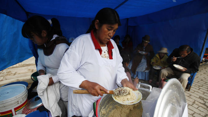 """In this Feb. 17, 2013 photo, a woman serves pesque, a traditional Andean plate made of cooked quinoa with cheese and milk at a street market in El Alto, Bolivia. A burgeoning global demand for quinoa is spurring new cultivation all across Bolivia's western highlands as prices for the Andean """"super grain"""" soar. But agronomists say quinoa fever is running up against physical limits. Quinoa does not lend itself to industrial-scale production and the rush to increase yields is prompting Bolivian growers to abandon traditional agricultural practices, thus endangering the fragile highlands' ecosystem. Bolivia's President Evo Morales will attend a U.N. event on Feb. 20 declaring 2013 the International Year of Quinoa. (AP Photo/Juan Karita)"""