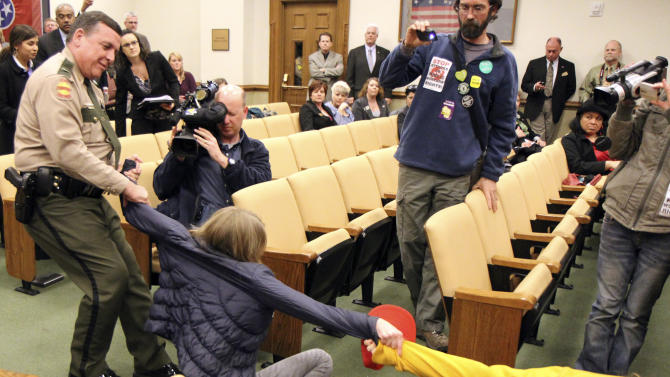 A state trooper pulls a pro-labor protesters who had disrupted a Senate Commerce Committee meeting in Nashville, Tenn., on Tuesday, March 15, 2011. Seven protesters were later charged with disorderly conduct and resisting arrest. (AP Photo/Erik Schelzig)