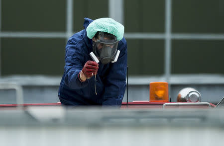 A man wearing a protective mask and suit inspects a container containing eggs and the bodies of culled chickens at a poultry farm, where a highly contagious strain of bird flu was found by Dutch authorities, in Hekendorp