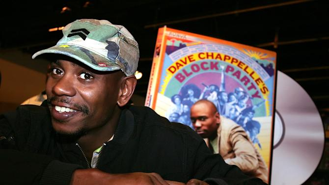 """FILE - In this June 13, 2006 file photo, comedian Dave Chappelle promotes the release of his new DVD """"Dave Chappelle's Block Party,"""" at the Virgin Megastore in Los Angeles. Chappelle will make his most substantial return to stand-up comedy in a month-long tour for Funny Or Die. The reclusive comedian will headline the Oddball Comedy and Curiosity Festival, which kicks off Aug. 23, 2013, in Austin, Texas. The 13-date, two-stage tour concludes Sept. 22 in Phoenix. (AP Photo/Stefano Paltera, File)"""