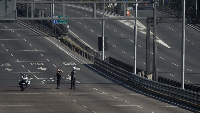Police stand on an empty highway that is blocked by protesters further down the road during a nationwide 24-hour general strike in Buenos Aires, Argentina, Tuesday, Nov. 20, 2012. Argentine President Cristina Fernandez is facing a nationwide strike, led by union bosses who once were her most steadfast supporters. Many trains and bus lines are paralyzed; banks, courts and schools are closed; airlines have canceled flights and small groups of people have blocked highways in about a dozen places around the capital. (AP Photo/Victor R. Caivano)