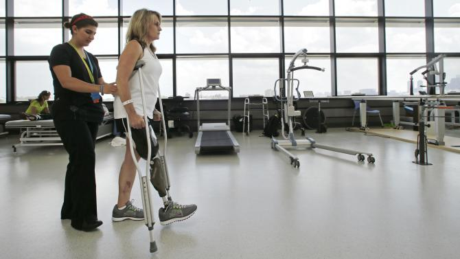 With physical therapist Dara Casparian, left, guiding her strides, Boston Marathon bombing survivor Roseann Sdoia, of Boston, looks forward towards a mirror at the Spaulding Rehabilitation Hospital, Friday June 20, 2013, in Boston. Sdoia went back to the hospital to learn to walk with her new leg. (AP Photo/Charles Krupa)
