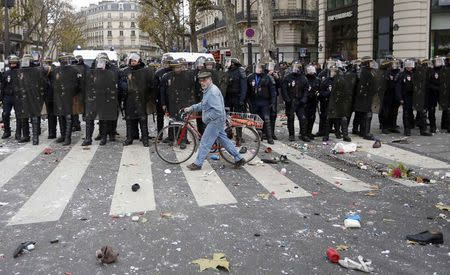 A man with a bicycle walks past CRS riot policemen after clashes with demonstrators at the Place de la Republique ahead of the World Climate Change Conference 2015 in Paris