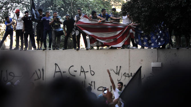 Egyptian protesters standing on the sidewall of the U.S. embassy move down an American flag pulled down from the embassy in Cairo, Egypt, Tuesday, Sept. 11, 2012. Egyptian protesters, largely ultra conservative Islamists, have climbed the walls of the U.S. embassy in Cairo, went into the courtyard and brought down the flag, replacing it with a black flag with Islamic inscription, in protest of a film deemed offensive of Islam. (AP Photo/Nasser Nasser)