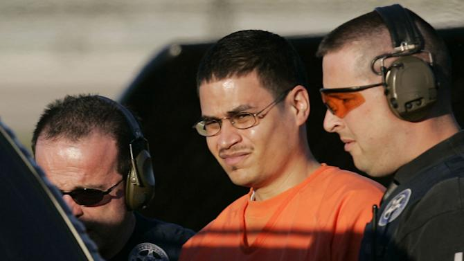FILE - In this Jan. 5, 2006 file photo, Jose Padilla, center, is escorted to a waiting police vehicle by federal marshals near downtown Miami. The 17-year prison sentence imposed on the convicted terrorism plotter is far too lenient for someone who trained to kill at an al-Qaida camp and also has a long, violent criminal history, a federal appeals court ruled Monday, Sept. 19, 2011, as it threw out the sentence. (AP Photo/J. Pat Carter, File)
