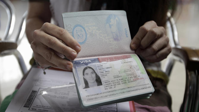 ADDS SANCHEZ IS SHOWING U.S. VISA ON HER PASSPORT.- Cuban dissident blogger Yoani Sanchez shows her U.S. visa on her passport before leaving Cuba to travel to Brazil and other countries at the Jose Marti International Airport in Havana, Cuba, Sunday, Feb. 17, 2013. Sanchez is one of the Cuban dissidents who applied for passports to go overseas under recently enacted travel reform. Her request was granted last month. By her own account Sanchez has on some 20 occasions been rejected for the exit visa that for decades was required of all islanders seeking to go abroad.(AP Photo/Franklin Reyes)