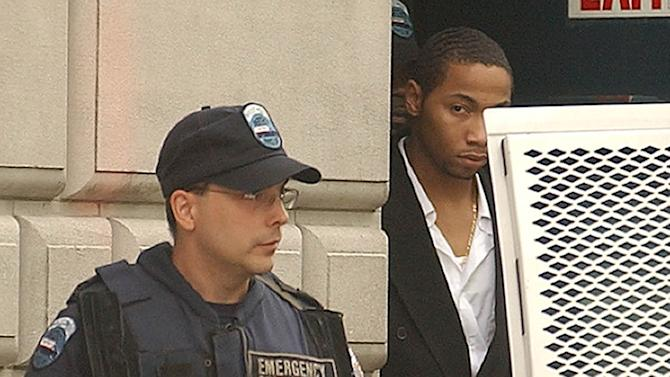 FILE- In this July 30, 2003 photo, Ronell Wilson, 21, of the Staten Island borough of New York, right, is escorted past a heavily armed corrections officer, after appearing in court to face charges of the March shooting death of two undercover police officers during a buy-and-bust operation. According to court papers file on Tuesday, Feb. 5, 2013, a federal prison guard had an illegal affair with Wilson at the Metropolitan Detention Center in New York, and is pregnant with his child. (AP Photo/Ed Betz, File)