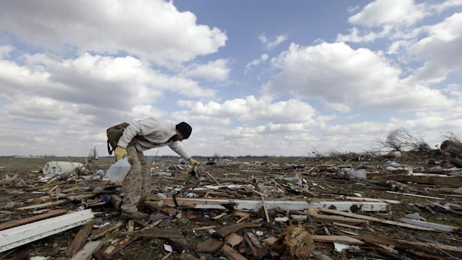 In this March 3, 2012 file photo, Jackson Hambree cleans up debris after a tornado struck in Marysville, Ind. Aiming to get people to safety sooner as a big storm approaches, the National Weather Service will expand that re-tooled severe weather warning system, from Kansas and Missouri to 12 more Midwestern states. Starting Monday, April 1, 2013, it will provide media outlets and emergency services with more detail about the strength of a brewing tornado or thunderstorm, what it may hit and when. (AP Photo/Nam Y. Huh)