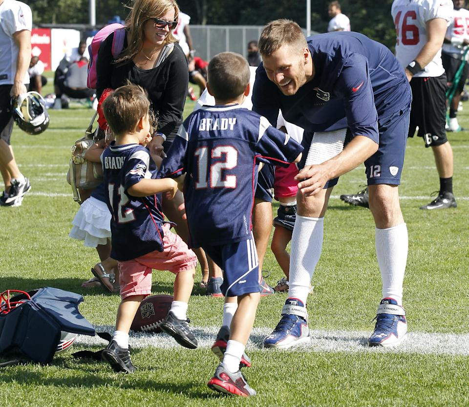 New England Patriots quarterback Tom Brady waits as his sons, John Moynahan, center, and Benjamin Brady, left, run to him following the Patriots' joint workout with the Tampa Bay Buccaneers at NFL football training camp, in Foxborough, Mass., Thursday, Aug. 15, 2013. (AP Photo/Stew Milne)