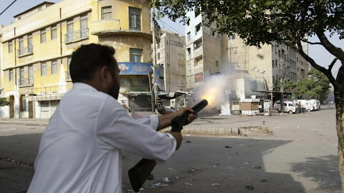 """A plain clothed Pakistani police officer fires a tear gas canister to disperse protesters, not shown, during clashes in Karachi, Pakistan, Friday, Sept 21, 2012. during clashes that erupted as the demonstrators tried to approach the U.S. embassy in Islamabad, Pakistan, Friday, Sept. 21, 2012. Demonstrations turned violent in several Pakistani cities and over a dozen people were killed as tens of thousands protested against an amateurish anti-Muslim film produced in the United States and vulgar caricatures of the Prophet Muhammad published in a French satirical weekly around the country after the government encouraged peaceful protests and declared a national holiday — """"Love for the Prophet Day."""" (AP Photo/Fareed Khan)"""