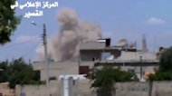 A image grab taken from a video uploaded on Youtube by Al-Qusayr Media Centre on May 22, 2013 shows smoke billowing from buildings in the city of Qusayr, in Syria's central Homs province, following an airstrike by government forces