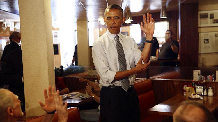 President Barack Obama talks about his basketball game with customers at Canter's Deli in Los Angeles, Thursday, July 24, 2014, where he made a surprise appearance on the final day of his three-day West Coast trip. (AP Photo/Los Angeles Times, Jay L. Clendenin, Pool)