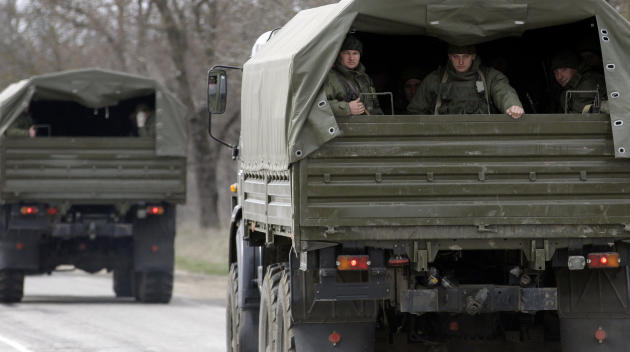 Uniformed men look out of military vehicles bearing no license plates as they travel on the road from Feodosia to Simferopol in the Crimea, Ukraine, Saturday, March 8, 2014. More than 60 military truc