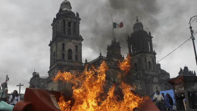 Members of the teachers' union CNTE and protesters stand near a burning barricade before they are evicted from Zocalo Square by the riot police in downtown Mexico City