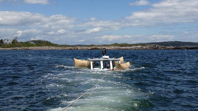 """In this handout photo provided by Verian Tuttle that was taken Sunday, June 9, 2013, the lobsterboat """"Queen Tut"""" owned by Philip Tuttle is floated and towed to a dock in Harpswell, Maine. Tuttle, a 90-year-old lobsterman, survived the sinking of his boat by swimming to a nearby island through the icy waters of the Gulf of Maine. (AP Photo/Verian Tuttle)"""