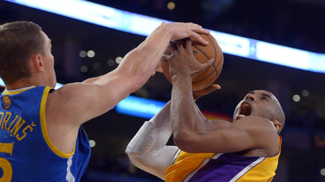 Golden State Warriors forward Andris Biedrins, of Latvia,, left, blocks the shot of Los Angeles Lakers guard Kobe Bryant during the first half of their NBA basketball game, Friday, April 12, 2013, in Los Angeles. (AP Photo/Mark J. Terrill)