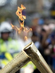 Torchbearers 'kiss' with their torches to pass the Olympic flame during the London 2012 torch relay through the Borough of Tower Hamlets in London