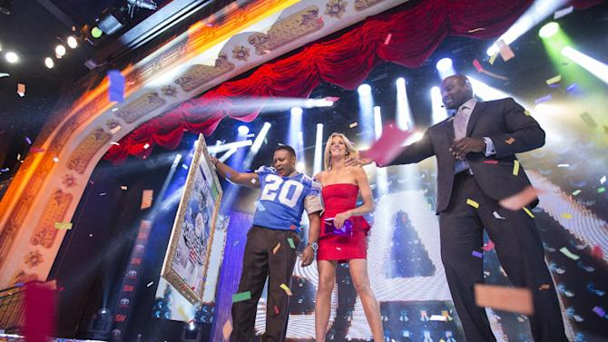 IMAGE DISTRIBUTED FOR EA SPORTS - NFL hall of fame running back Barry Sanders, left, holds up a mock up of the Madden 25 video game cover while co-hosts Charissa Thompson, center, and Marcellus Wiley, right look on during the EA Sports Madden NFL 25 Cover Reveal on SportsNation on Wednesday, April, 24, 2013 in New York. (Photo by Chris Park/Invision for EA Sports/AP Images)
