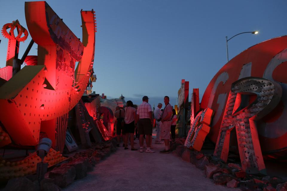 Tourists look at old hotel and casino signs at the Neon Museum in Las Vegas on Friday, May 24, 2013. For the past six months, tourists have had to squint up at the hulking metal forms through the desert sun. On Friday, the museum unveiled nighttime hours. (AP Photo/Julie Jacobson)