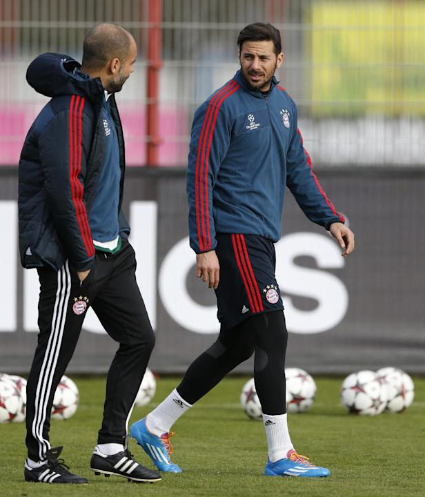Bayern head coach Pep Guardiola of Spain, left, talks to Claudio Pizarro of Peru as he arrives for a last training session prior the Champions League group D soccer match between FC Bayern Munich and