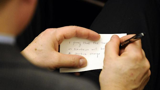 A man writes a prayer for Newtown on a note card during an interfaith sermon at Newtown Congregational Church in Newtown, Conn., Sunday, Jan. 20, 2013. Forbes, who led one of the country's most prominent liberal Protestant churches,  is speaking in Newtown to honor the victims of last month's school shooting and the legacy of the Rev. Martin Luther King Jr. (AP Photo/Jessica Hill)