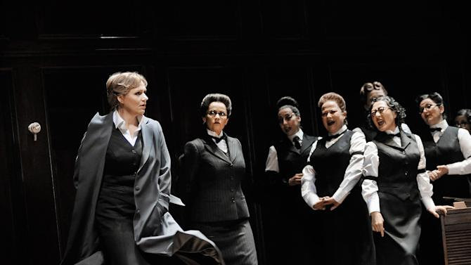"""In this undated photo provided by the Opernhaus Zurich Anja Kampe in the role of Senta, left, performs on stage withe the choir during a dress rehearsal for Richard Wagner's opera """"Der fliegende Hollaender"""" (The Flying Dutchman) at the opera in Zurich, Switzerland. (AP Photo/Opernhaus Zurich/T+T Fotografie/Toni Suter + Tanja Dorendorf)"""