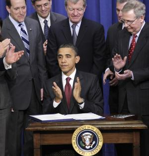President Barack Obama, joined by Republican and Democratic lawmakers including Senate Republican leader Mitch McConnell of Kentucky at right, looks up after signing the bipartisan tax package that extends tax cuts for families at all income levels, during a signing ceremony at the Eisenhower Executive Office Building in the White House complex, Friday, Dec. 17, 2010, in Washington. Aimed at helping to stabilize the recovering economy, the bill keeps in place tax cuts instituted by President George W. Bush for another two years. (AP Photo/J. Scott Applewhite)