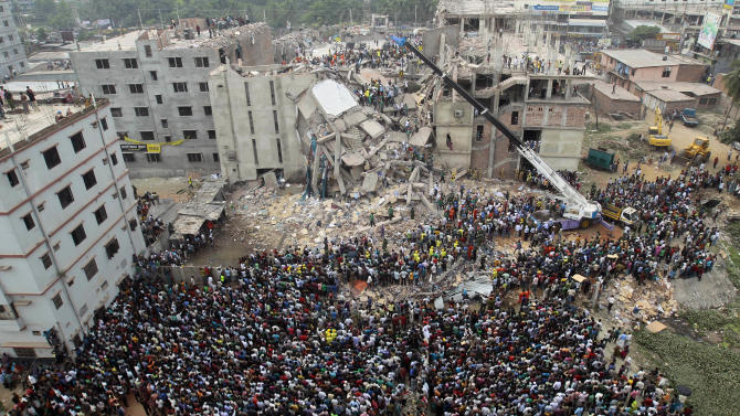 FILE - In this April 25, 2013 file photo, Bangladeshi people gather as rescuers look for survivors and victims at the site of a building that collapsed a day earlier, in Savar, near Dhaka, Bangladesh. The owner of the building sits at the nexus of party politics and the powerful $20 billion garment industry that drives the economy of this deeply impoverished nation. Experts say this intersection of politics and business, combined with a minimum wage of $9.50 a week that has made Bangladesh the go-to nation for many of the world's largest clothing brands, has created a predictable danger for factory workers. Government officials, labor activists, manufacturers and retailers all called for improved safety standards after a November fire in the same suburb, when locked emergency exits trapped hundreds of garment workers inside amid spreading flames and 112 people died. But almost nothing has changed. (AP Photo/A.M.Ahad, File)