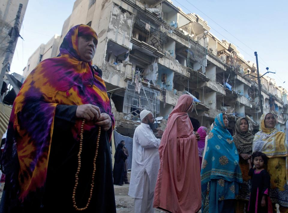 People gather at the site of a Sunday car bombing that killed dozens of people, in Karachi, Pakistan, Monday, March 4, 2013. Members of Pakistan's Shiite community were digging Monday through the rubble of a massive car bombing that targeted members of the minority sect leaving a mosque. (AP Photo/Shakil Adil)