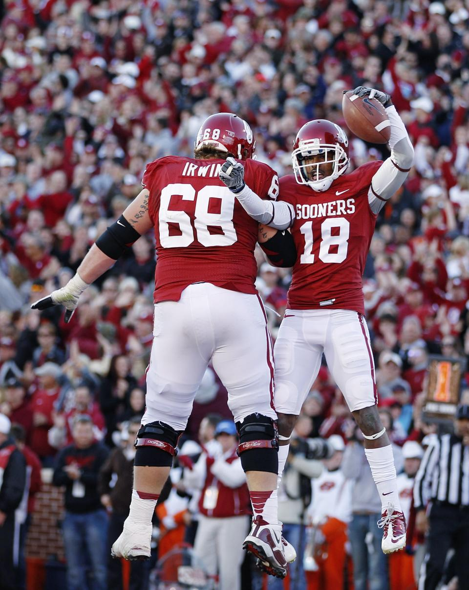 Oklahoma wide receiver Jalen Saunders (18) celebrates with offensive lineman Bronson Irwin (68) after scoring a touchdown against Oklahoma State in the second quarter of an NCAA college football game in Norman, Okla., Saturday, Nov. 24, 2012. (AP Photo/Sue Ogrocki)