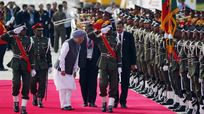 Indian Prime Minister Manmohan Singh bows in front of a flag of India and Maldives during a guard of honor after his arrival in Addu, Maldives, Wednesday,  Nov. 9, 2011. The heads of eight South Asian Association for Regional Cooperation (SAARC) countries are meeting in this Indian Ocean archipelago on Nov. 10 and 11. (AP Photo/Sinan Hussain)