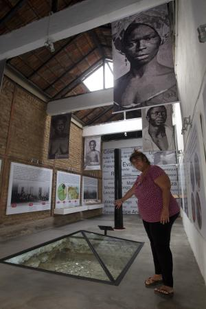 "In this Sept. 11, 2012 photo, Ana de la Merced Guimaraes points to remains of African slaves covered with a glass pyramid at her home in Rio de Janeiro, Brazil. In 1996, Merced Guimaraes and her husband Petrucio bought a fixer-upper in the historic port-side neighborhood of Gamboa. Once they started digging into the foundation, they made a startling discovery: the building sat atop the ""cemetery of new blacks,"" - the burial place of newly arrived Africans who died soon after their arrival in Brazil between 1769 and 1830. (AP Photo/Silvia Izquierdo)"