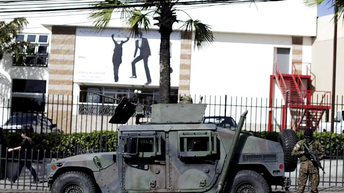 Army vehicle patrols near a shopping mall during the fourth day of a suspension of public transport services in San Salvador