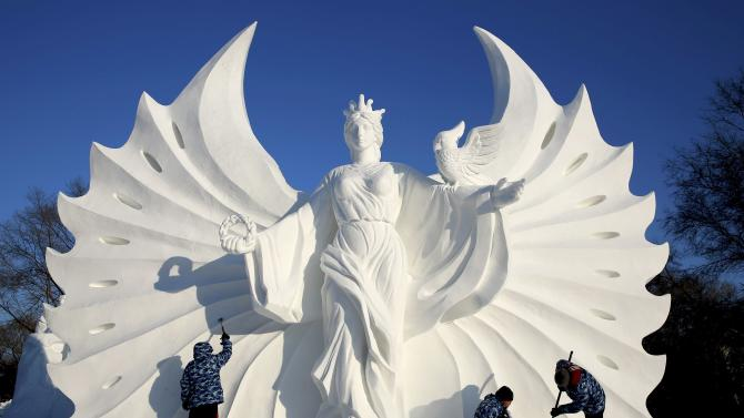 Workers polish a snow sculpture ahead of the 16th Harbin Ice and Snow World in Harbin