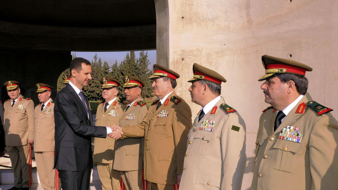 FILE - In Oct. 6, 2012 file photo released by the Syrian official news agency SANA, Syrian President Bashar Assad greets military officers in a ceremony marking the anniversary of the 1973 Arab-Israeli war in Damascus, Syria. With even his most powerful ally, Russia, losing faith in him, President Bashar Assad may appear to be heading for a last stand against rebel forces who have been waging a ferocious battle to overthrow him for nearly two years. But Assad still has thousands of elite and loyal troops behind him, and analysts say that even if he wanted to give up the fight, it's unclear those around him would let him abandon ship and leave them to an uncertain fate.(AP Photo/SANA, File)