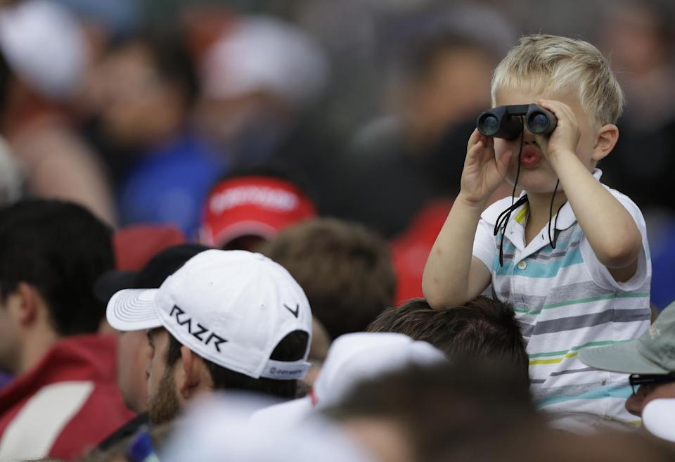 Spectators watch Rory McIlroy of Northern Ireland on the fourth green as a boy with binoculars watches the opposite direction at Royal Lytham & St Annes golf club during the second round of the British Open Golf Championship, Lytham St Annes, England, Friday, July 20, 2012. (AP Photo/Tim Hales)