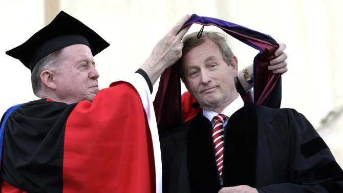 Irish Prime Minister Enda Kenny, right, is hooded by Boston College President William P. Leahy as he receives an honorary Doctor of Laws degree during commencement ceremonies at Alumni Stadium in Boston, Monday, May 20, 2013. Cardinal Sean O'Malley skipped Boston College's commencement Monday because of the involvement of Kenny, who supports a bill in his country that would allow abortion. The leader of the Boston Archdiocese traditionally gives the benediction at the college's ceremony. (AP Photo/Elise Amendola)