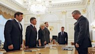 Russia&#39;s Prime Minister Dmitry Medvedev (2nd R) and officials hold a minute&#39;s silence in Moscow to mourn the victims of the flood in the southern Krasnodar region. The first head rolled Monday over the floods in southern Russia that killed at least 171 people as the authorities blamed local officials for failing to warn locals in time of the looming calamity