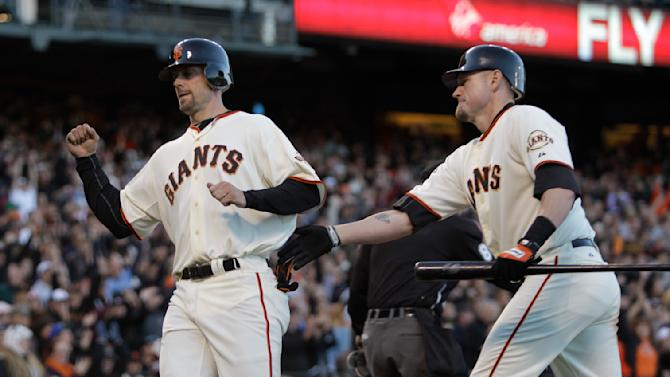 San Francisco Giants' Chris Stewart, left, and Aubrey Huff celebrate as Stewart crosses the plate to score against the Cincinnati Reds during the seventh inning of a baseball game Sunday, June 12, 2011, in San Francisco. Stewart scored on a sacrifice fly by Nate Schierholtz. (AP Photo/Ben Margot)