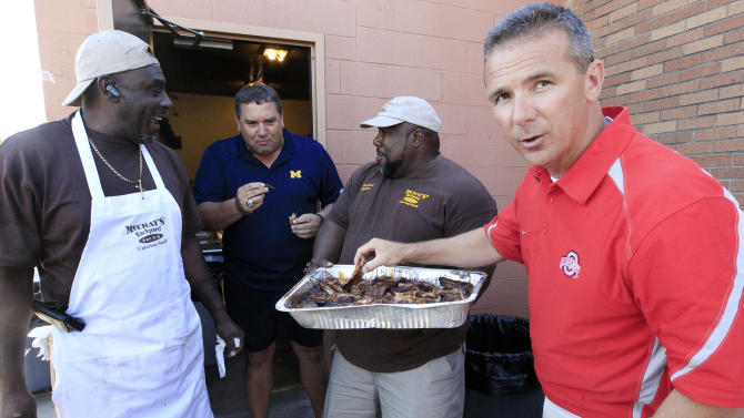 Michigan head football coach Brady Hoke, second from left, and Ohio State head football coach Urban Meyer, right, sample ribs from Gerald Wright, left, and Derrick McCray at the eighth annual Sound Mind, Sound Body Football Academy at the Southfield High School in Southfield, Mich., Wednesday, June 13, 2012. Meyer and Hoke were two of a handful of college coaches who were on hand at the camp, which draws kids from all over the country. (AP Photo/Carlos Osorio)