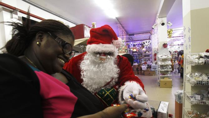 A man dressed as Santa Claus gives sweets to a customer at the Orca supermarket in Marcory in Abidjan