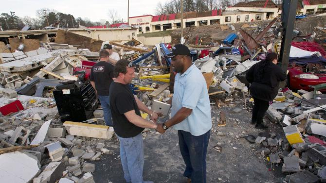 The Rev. Herman Henderson, right, prays with Brent Cherry in the middle of his destroyed business in Center Point, Ala., Monday, Jan. 23, 2012. Jefferson County sheriff's spokesman Randy Christian said the storm produced a possible tornado that moved across northern Jefferson County around 3:30 a.m., causing damage in Oak Grove, Graysville, Fultondale, Clay and Trussville.  (AP Photo/Dave Martin)