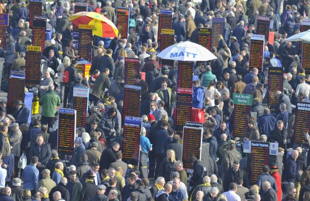 Racegoers walk amongst the betting stands during the Cheltenham Festival horse racing meet in Gloucestershire, western England