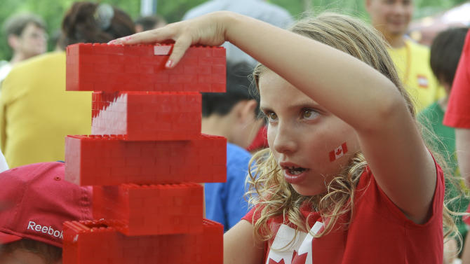 IMAGE DISTRIBUTED FOR LEGO SYSTEMS, INC - Emma Lebrun stacks bricks to be added to the Canada Day LEGO Flag, on Monday July 1, 2013 at Parc Jacques-Cartier Park in Gatineau, Quebec. For Canada Day, children could help build a Canadian flag made out of 128,000 LEGO bricks. (Francis Vachon / AP Images for LEGO Systems, Inc.)