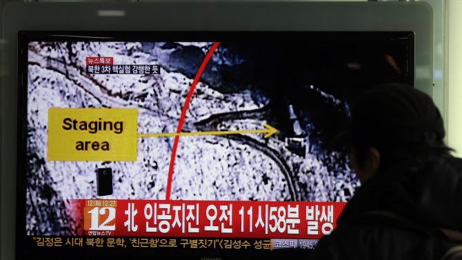 """A South Korean passenger watches TV news reporting an earthquake in North Korea, at the Seoul train station in Seoul, South Korea, Tuesday, Feb. 12, 2013. The U.S. Geological Survey on Tuesday detected a magnitude 4.9 earthquake in North Korea. Neither Pyongyang nor Seoul confirmed whether North Korea had conducted its widely anticipated third nuclear test, though an analyst in Seoul said a nuclear detonation was a """"high possibility."""" The Korean letters on the screen read: """"North, artificial earthquake 11:58 a.m."""" (AP Photo/Lee Jin-man)"""