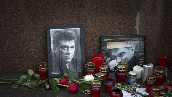 "Flowers, votive candles and portraits are seen at the place where Boris Nemtsov, a charismatic Russian opposition leader and sharp critic of President Vladimir Putin, was gunned down on Friday, Feb. 27, 2015 near the Kremlin, in Moscow, Russia, Thursday, March 5, 2015. President Vladimir Putin on Wednesday called the slaying of his top critic a ""disgrace"" to Russia, while the opposition promised to complete Nemtsov's work on a report documenting evidence of Russian troops' involvement in fighting in eastern Ukraine. (AP Photo/Alexander Zemlianichenko)"
