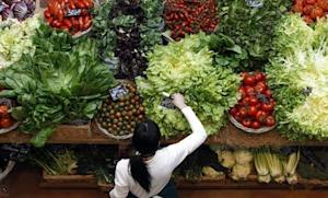 Employee arranges pricetags at vegetables work bench during the opening day of upmarket Italian food hall chain Eataly's flagship store in downtown Milan